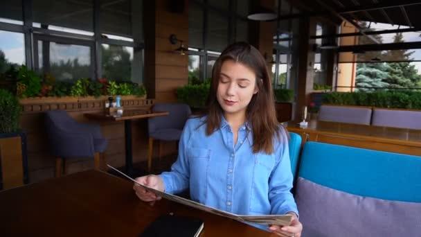 Hezká žena čte menu v restauraci s zblízka obličej v pomalém pohybu