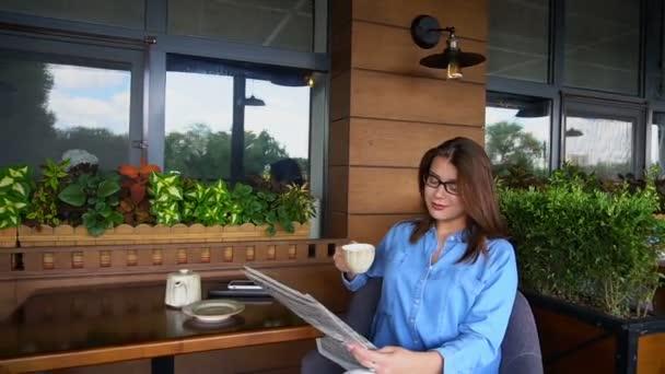Okouzlující žena, čtení novin v restauraci a pití čaje ve zpomaleném záběru