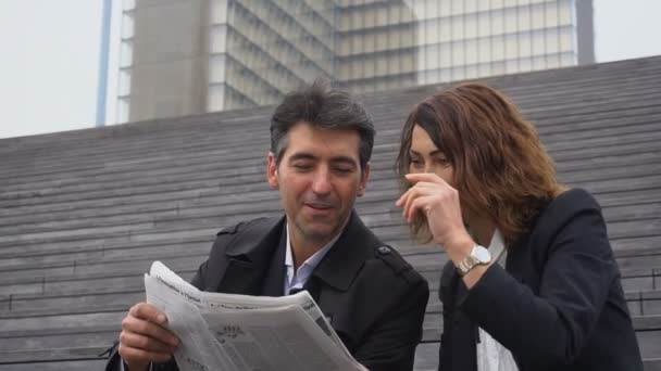 Slow motion engineers male and female reading article about company in newspaper.