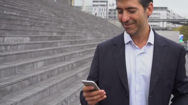Slow motion obchodní muž chůze pomocí smartphone sledovat fotografie.