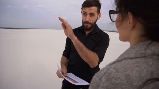 Zpomalený pohyb podnikatelů samec a samice se o projektu uspořádání pláž u moře