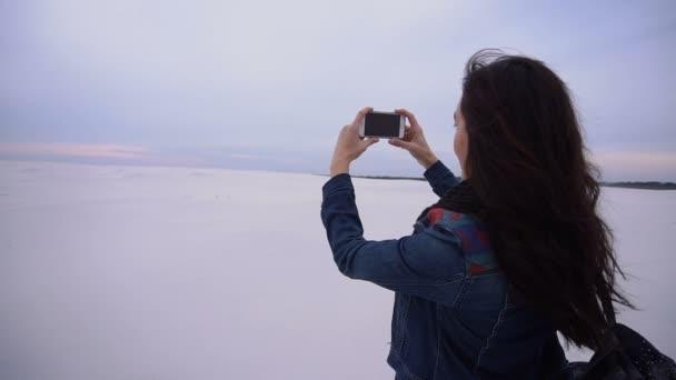 Slow motion cestovatel dívka pomocí smartphonu fotí západ slunce.