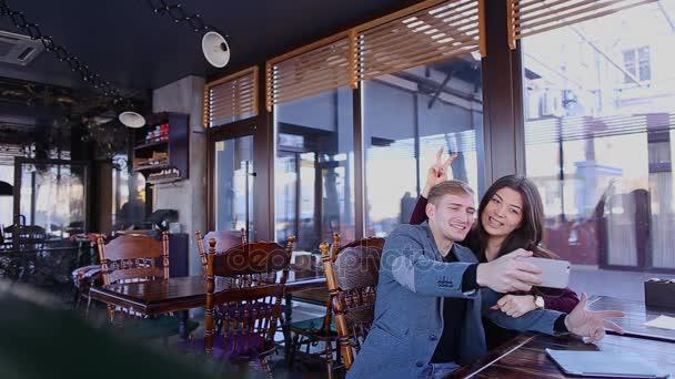Így selfie a kamera elé néz smartphone kávézóban pár