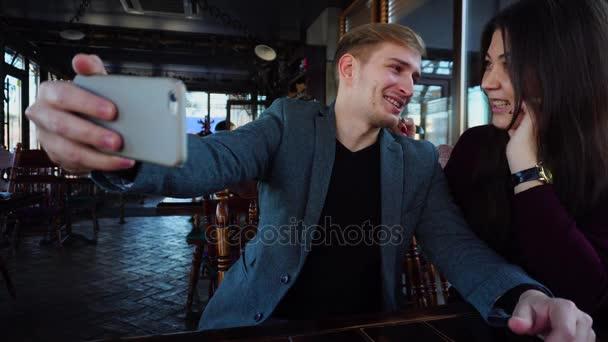 Girlfriend and boyfriend sitting in cafe taking selfie with smartphone.