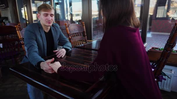 Couple sitting in luncheonette holding hands and discussing new working place for girl.