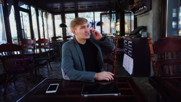 Businessman sitting near table with smartphone and laptop speaking on phone