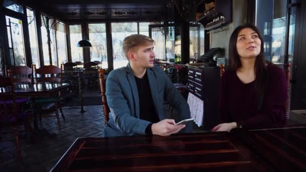 Girlfriend and boyfriend with smartwatch discussing design of own coffee house and taking photos using smartphone.
