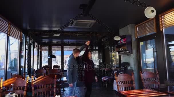 Mladý pár, tanec v kavárně na oslavu narozenin.
