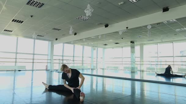 Young dancer sitting on twine and doing stretching