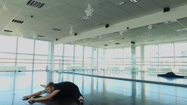 Dance trainer sitting on twine with tilts forward