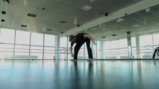 Blonde dancer in black suit working out at gym studio.