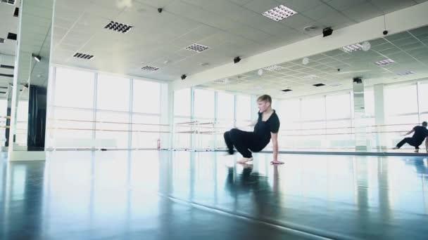 Guy making break dance movements in slow motion.
