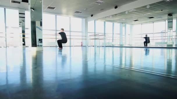 Guy making somersault backwards in slow motion at studio