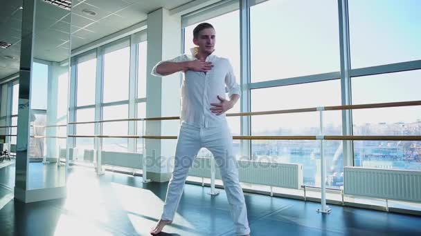 Young blonde dancer enjoys winning in white suit and makes warm up.