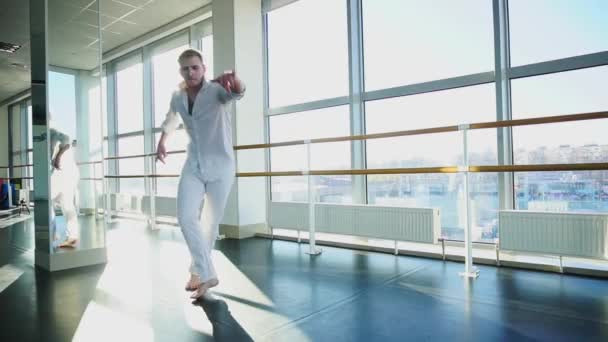 Blonde guy doing vigorous movements in white suit.