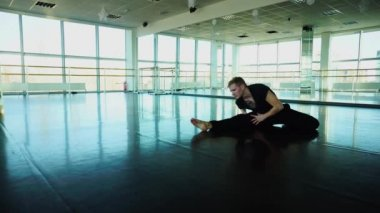 Professional dancer in sportswear doing stretching exercises in gym