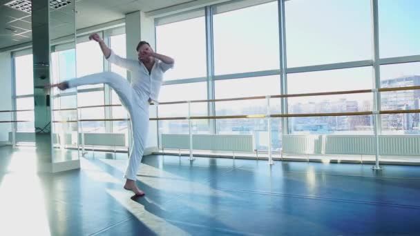 Man raising legs high in slow motion at studio