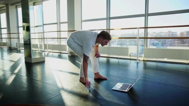 Male person learning new movements with laptop at gym