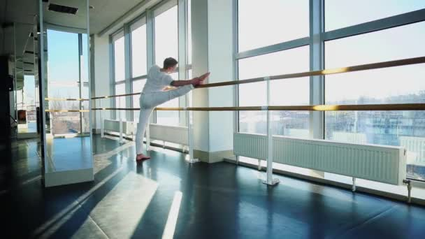Young person making leg stretching near window