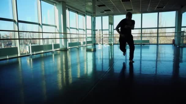 Medical student in sportswear rehearsing dance in hall.