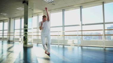 Rehabilitation specialist in sportswear dance during photoshoot in gym
