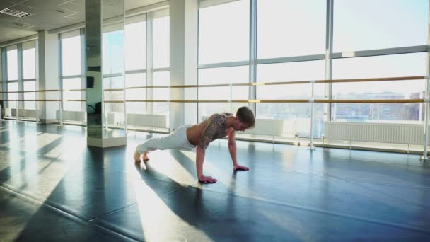 Lawyer with good body in sportswear doing different pushups in gym