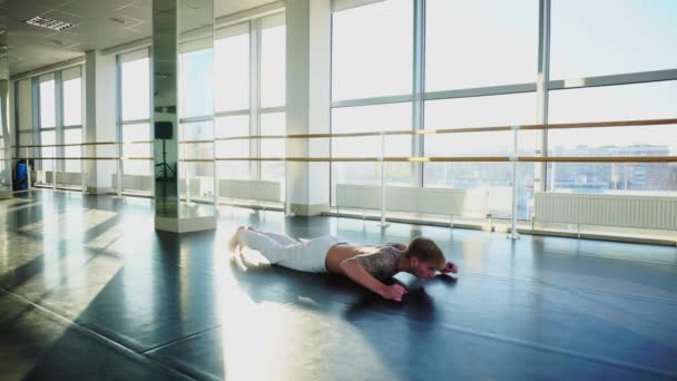 Faculty of physical education student in sportswear diligently doing pushups in hall