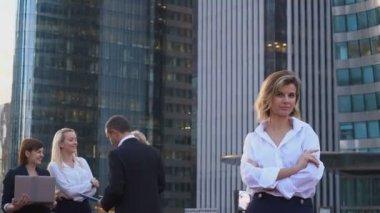 Secretary looking at camera with team members background in La Defense Paris.