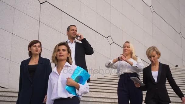 Finanční tým jde dolů po schodech v pomalém pohybu s tabletem, případ a mluví o smartphone