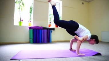 Beautiful girl doing stretching exercises and yoga asanas.