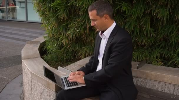 Businessman working with laptop outside near plant in slow motion.