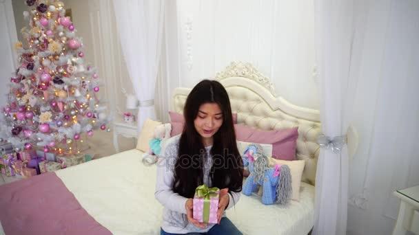 Krásná dívka v Silvestrovské náladě s darem v rukou usmívá na fotoaparátu a sedí na posteli v pozadí vánočního stromu v růžové ložnici