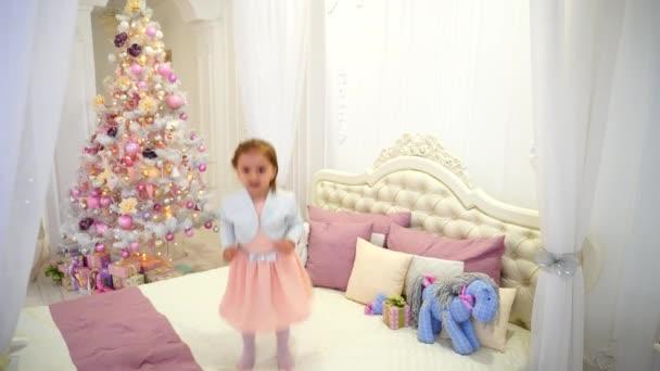 Mignonne petite fille ayant amusant et sautant sur le lit dans la ...