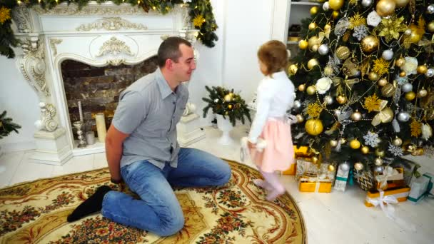 Young Adult Dad With Little Daughter Exchange Gifts and Hugging Each Other in Large Room on Background of Decorated Fireplace and Christmas Tree.