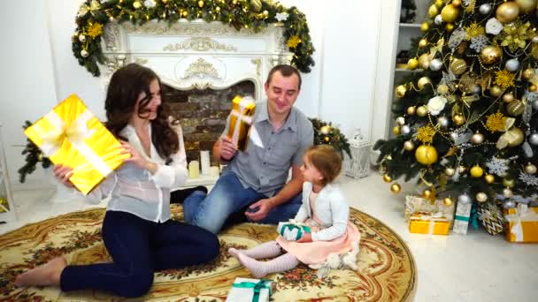 Lovely Family Holiday Within Temptation Exchange Gifts in Large Bright Room on Background of Festive Trees and Beautifully Decorated Fireplace.