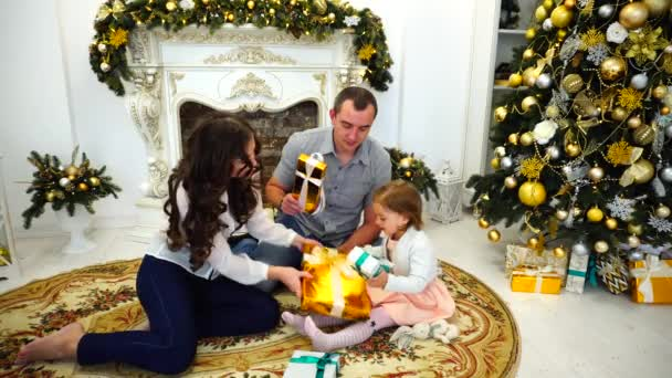 Cheerful Family Holiday Within Temptation Happy Together and Give Gifts in Large Room on Background of Festive Trees and Decorated Fireplace.