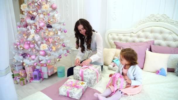 Junge Mutter Und Töchterchen Vorbereitung Für Neue Jahresferien In  Geräumigen Hellen Schlafzimmer Sitzt Auf Bett Vor
