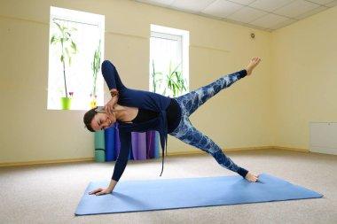 Businesswoman studies basic yoga exercises on online course.