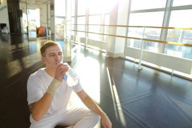 Guy doing drinking water before morning training.