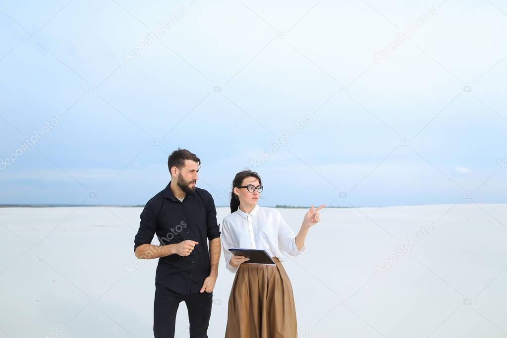 Engineers male and female designing pond in desert.