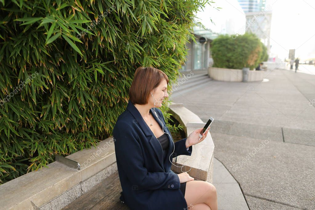 Businesswoman typing message and listening to music outside with