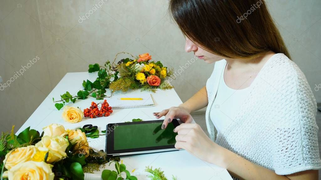 Charming girl florist looks at  tablet trends of  season when co