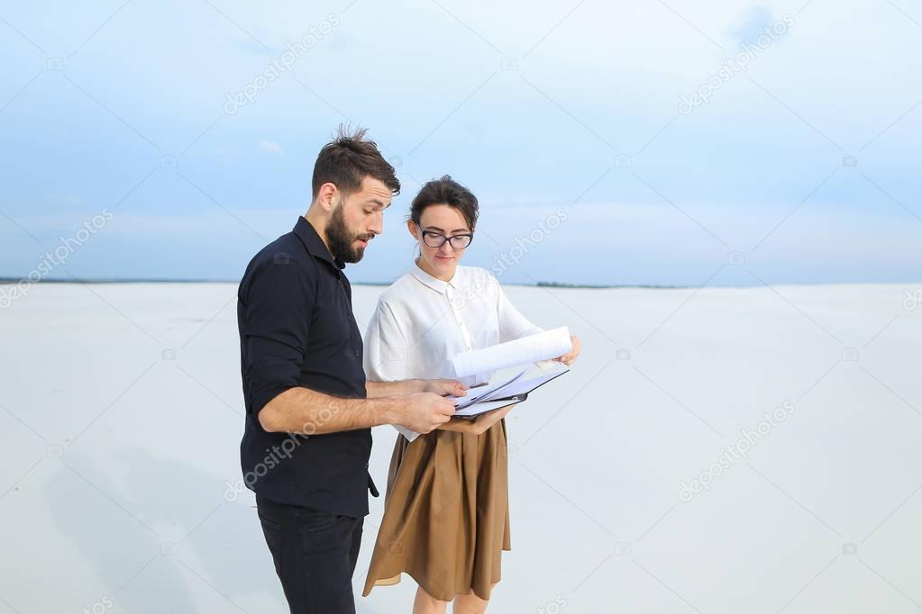 Landscape designer woman showing sketches to customer man.