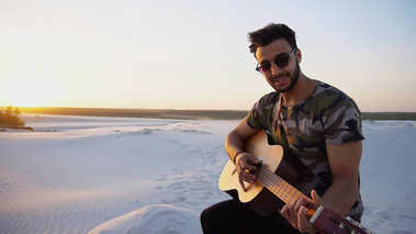Handsome Arabian guy playing guitar, standing on hill among sand