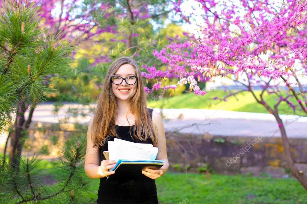 Businesswoman in glasses keeping documents near blooming trees in garden.