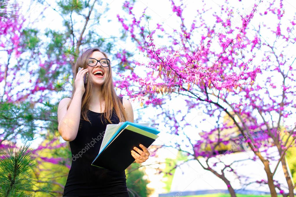 Young businesswoman talking with partner by smartphone near blooming trees.
