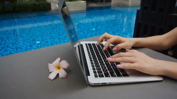 lose up hands chatting on laptop keyboard with swimming pool in slow motion.