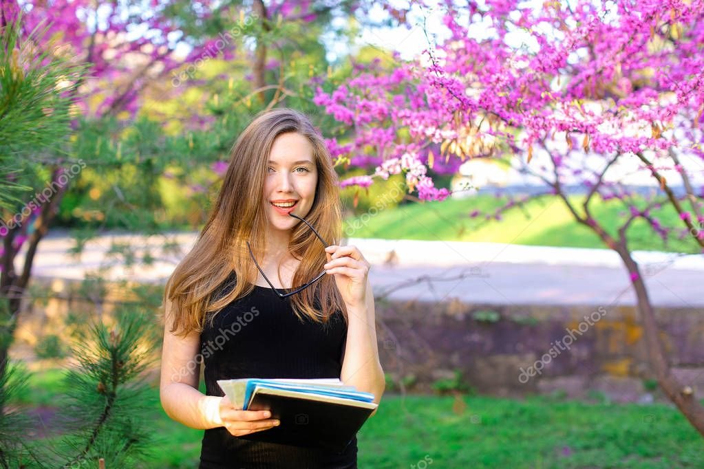 Female teacher standing in park with glasses and documents near blooming trees.