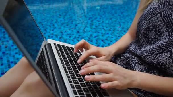 Közelről laptop és a gépelés üzenet, úszómedencével háttérrel, lassítva kezek.