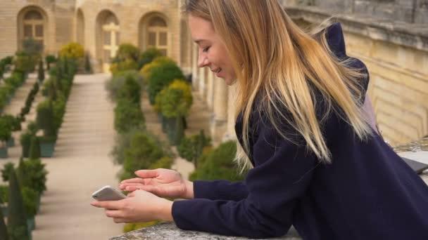 Okouzlující žena stojící s smartphone a udržování Beruška na straně s pozadím Versailles